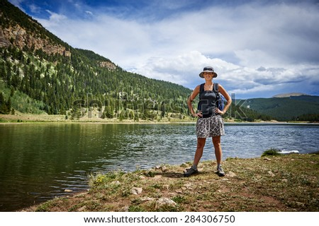 young woman hiking next to a mountain lake - stock photo
