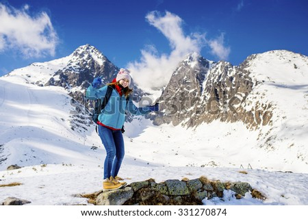 Young woman hiking outside in sunny winter mountains - stock photo