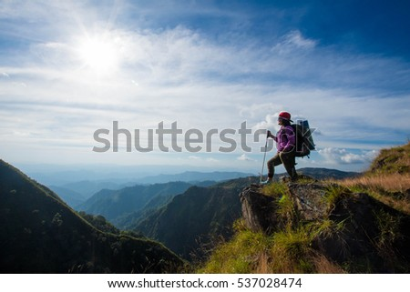 young woman hiking stand looking view on top mountain at sunny day. subject is blurred