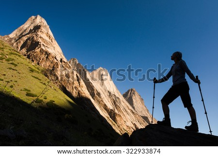 Young woman hiking (trekking) in spectacular high mountains, Kyrgyzstan, Central Asia