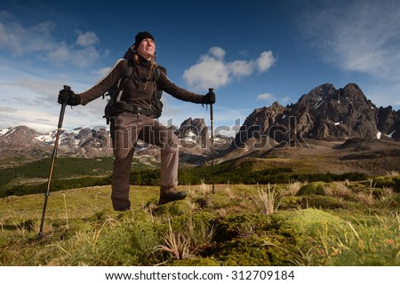 Young woman hiking (trekking) in spectacular high mountains, Patagonia, Chile - stock photo
