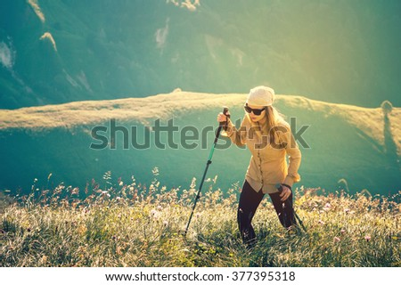 Young Woman hiking with trekking poles Travel Lifestyle concept Summer journey vacations outdoor mountains on background - stock photo