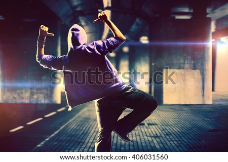 Young woman hip-hop dancer on urban background with flare effects - stock photo