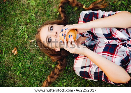 Young woman hipster lying on the grass and eating a hamburger. A girl enjoys the food, eating. The teenager went outside during a break and eats. Dressed in a plaid shirt, hair style braids
