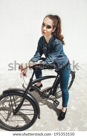 Young woman hipster standing with black bike. Outdoor lifestyle portrait