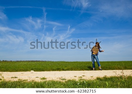 Young woman hitch hiking on a beautiful green meadow