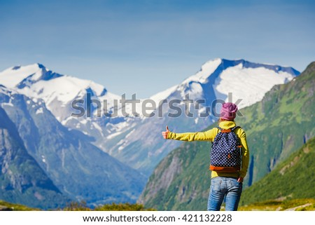 young woman hitchhiking on mountain road - stock photo