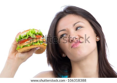 Young woman hold burger sandwich in hand hungry getting ready to eat isolated on a white background - stock photo