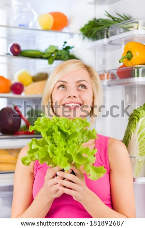 young woman hold fresh green salad diet think look up, refrigerator open door, pretty ponder girl dieting dream healthy food vegetables and fruits