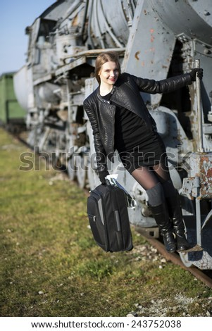 Young woman hold on train with left hand - stock photo