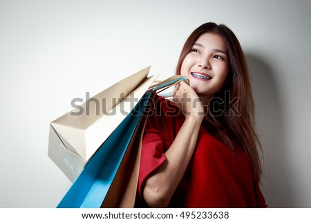 Young woman hold shopping bags. white background portrait.