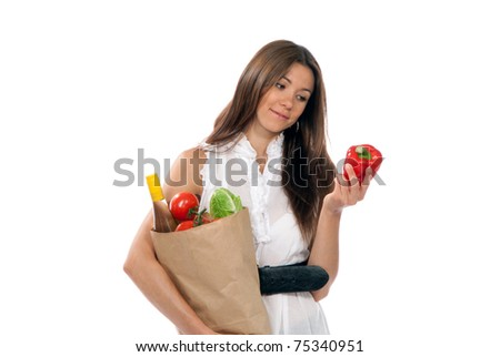Young woman hold shopping paper bag full of vegetarian groceries, red pepper in hand, salad, bottle of dry wine, orange, tomatoes  isolated on white background - stock photo