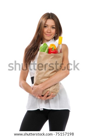 Young woman hold shopping paper bag full of vegetarian groceries, red pepper, salad, bottle of dry wine, orange  isolated on white background - stock photo