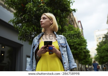 Young woman hold smart phone standing on mandarin tree background in the city, lost female tourist using telephone for navigation checking out the sights,student girl browsing internet on mobile phone - stock photo