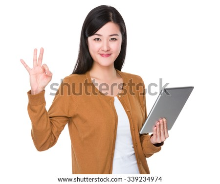 Young Woman hold with tablet and ok sign gesture - stock photo