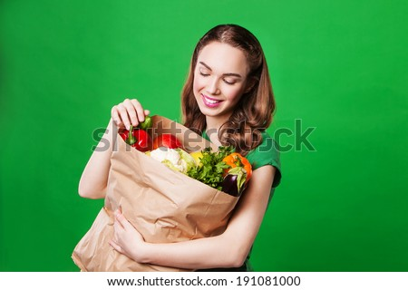 young woman holding a bag full of healthy food. shopping