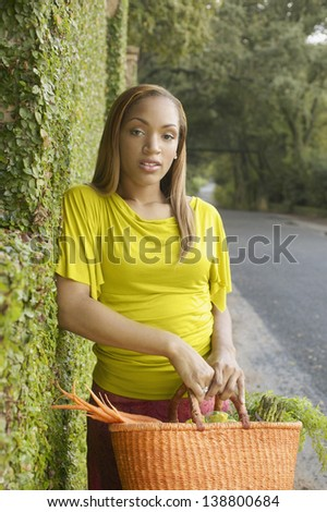 Young woman holding a basket of vegetables - stock photo