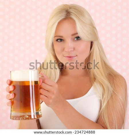 Young woman holding a beer - stock photo
