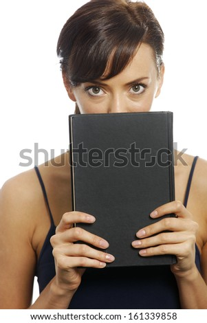 Young woman holding a black book over her face