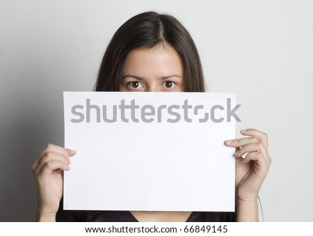 Young woman holding a blank sign in front oh her face - stock photo