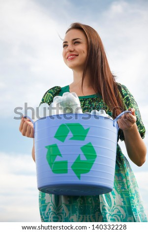 Young woman holding a blue recycling bin with plastic bottles