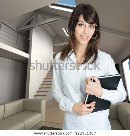 Young woman holding a book standing on a home interior