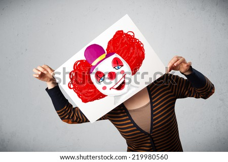 Young woman holding a cardboard with a clown on it in front of her head - stock photo