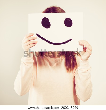 Young woman holding a cardboard with a smiley face on it in front of her head. Photo with instagram style filters - stock photo