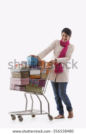 Young woman holding a cart full of gifts