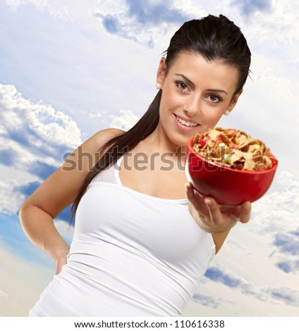 Young woman holding a cereal bowl, outdoor - stock photo
