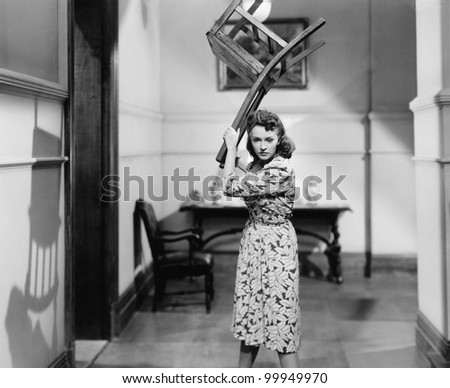 Young woman holding a chair above her head in anger - stock photo