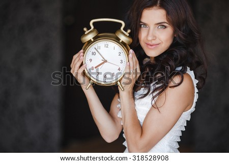 young woman holding a clock. time management concept. Young caucasian woman with alarm clock in her hands. picture of woman holding clock - stock photo