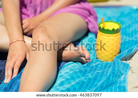 Young woman holding a colorful drink cup on a beach. Sitting in the sand with a pineapple shaped plastic glass, yellow and green color. Girl holding a refreshing beverage in her hands on a sunny day.
