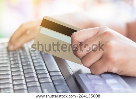 Young woman holding a credit card and typing. Online shopping. - stock photo