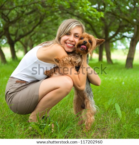 Young woman holding a cute dog - stock photo