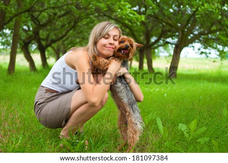 Young woman holding a dog in the park - stock photo