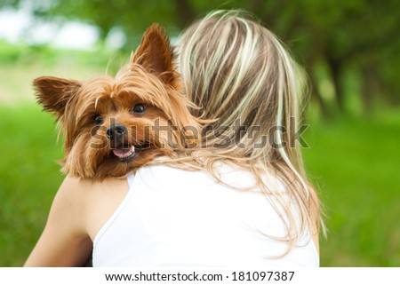 Young woman holding a dog in the park