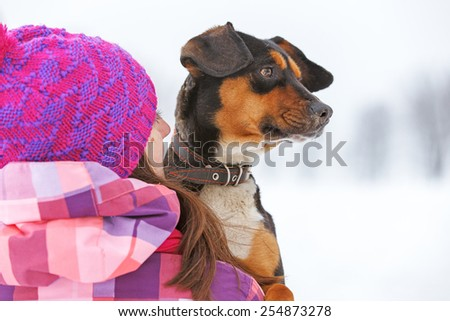 Young woman holding a dog looking in the same direction. - stock photo