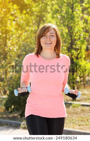 Young woman holding a dumbbell for fitness. Woman involved in sports and fitness in nature. Sports fitness outdoors. Active lifestyle urban dweller. Exercise at the city park. Fitness instructor. - stock photo