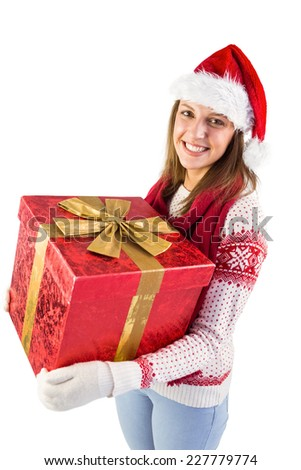 Young woman holding a gift while smiling at camera on white background