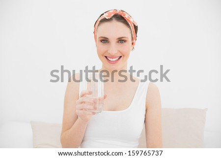 Young woman holding a glass of water smiling into the camera sitting on her bed