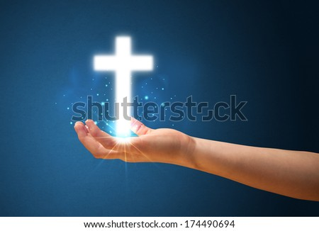 Young woman holding a glowing cross in her hand - stock photo