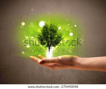 Young woman holding a glowing tree in her hand - stock photo