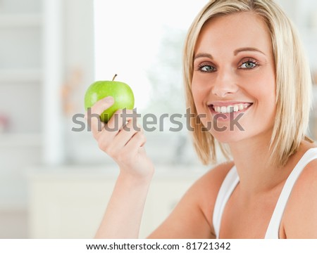 Young woman holding a green apple looking into the camera in the kitchen