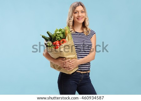 Young woman holding a grocery bag and looking at the camera on blue background