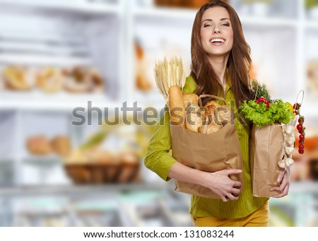 Young woman holding a grocery bag full of bread - stock photo