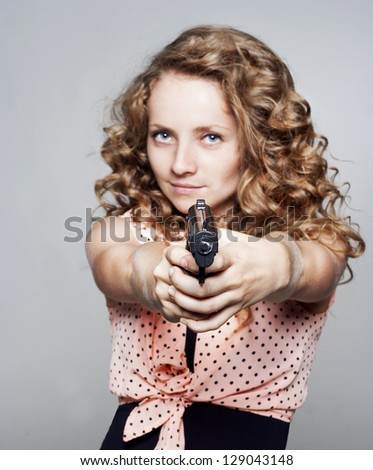 Young woman holding a gun - stock photo