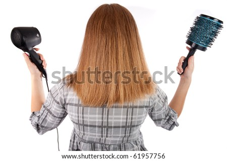Young woman holding a hairdryer and a brush,isolated on white - stock photo