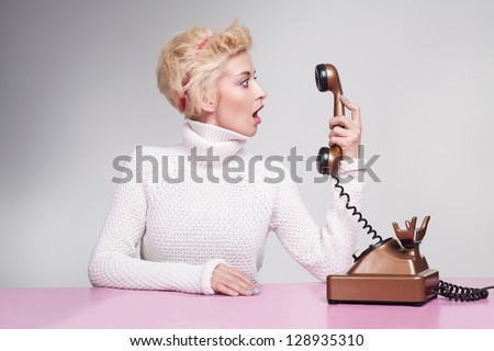 young woman holding a handset and looking at t with her mouth open - stock photo