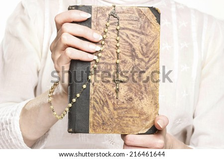 Young woman holding a Holy Bible and rosary - stock photo